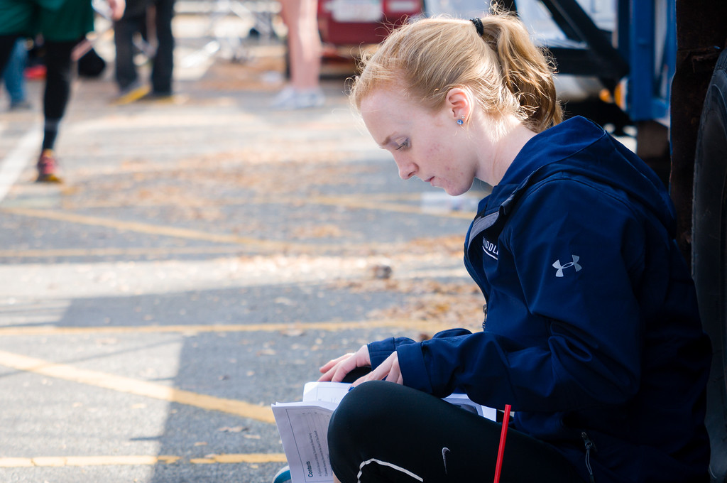 "October 21, 2012 - Caroline Moynihan, the new freshman coxswain for the Middlebury varsity men's eight boat at the Head of the Charles Regatta on Sunday, studies a map of the course before race time. Moynihan, who began coxing just three weeks ago, said she was ""very nervous"" about her first big race. According to former Assistant Coach Evan Doyle, ""The race can be won or lost by the coxswain"" due to the course's many technical turns. Photo/Christopher Weigl"