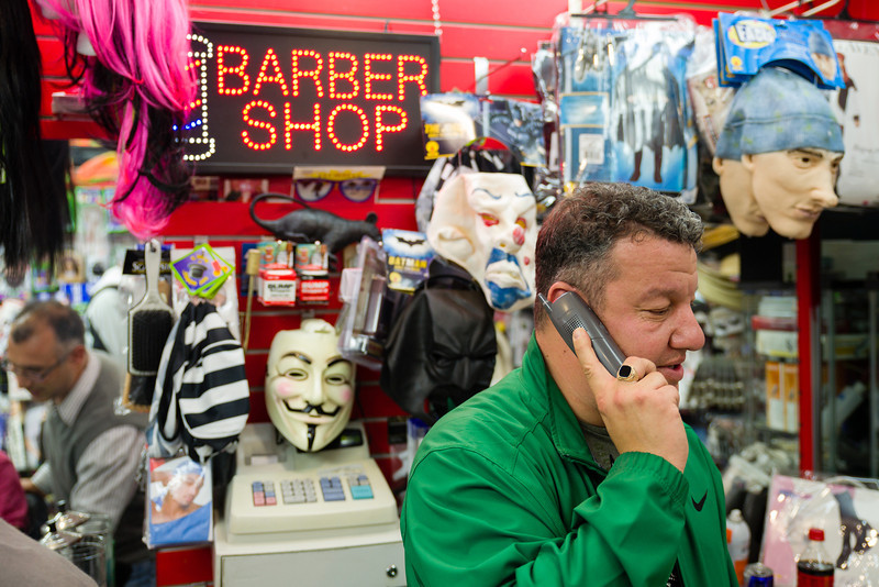 """October 25, 2012 - Richard Lamoretti, the owner of Fast Eddie's Barber Shop on Harvard Avenue in Allston, talks on the phone while longtime employee Eduard Achildiyer, reflected in the mirror at left, cuts a customer's hair.  Having worked at the family shop for 22 years now, Lamoretti said, """"I'm emotionally attached to the place, it's like my home."""" Photo/Christopher Weigl"""