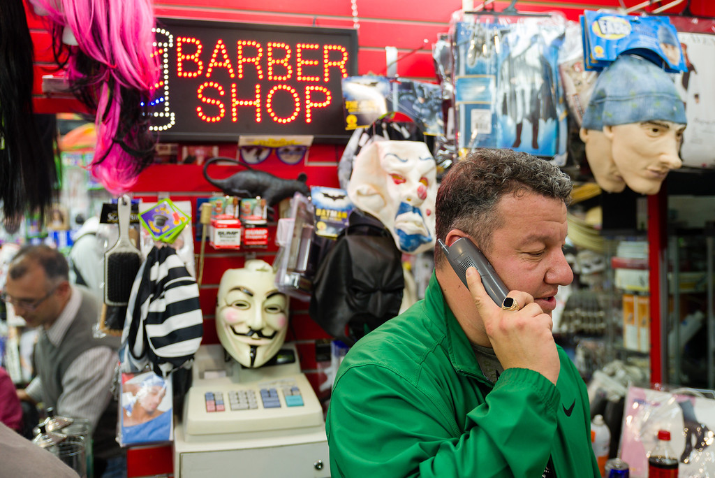 "October 25, 2012 - Richard Lamoretti, the owner of Fast Eddie's Barber Shop on Harvard Avenue in Allston, talks on the phone while longtime employee Eduard Achildiyer, reflected in the mirror at left, cuts a customer's hair.  Having worked at the family shop for 22 years now, Lamoretti said, ""I'm emotionally attached to the place, it's like my home."" Photo/Christopher Weigl"