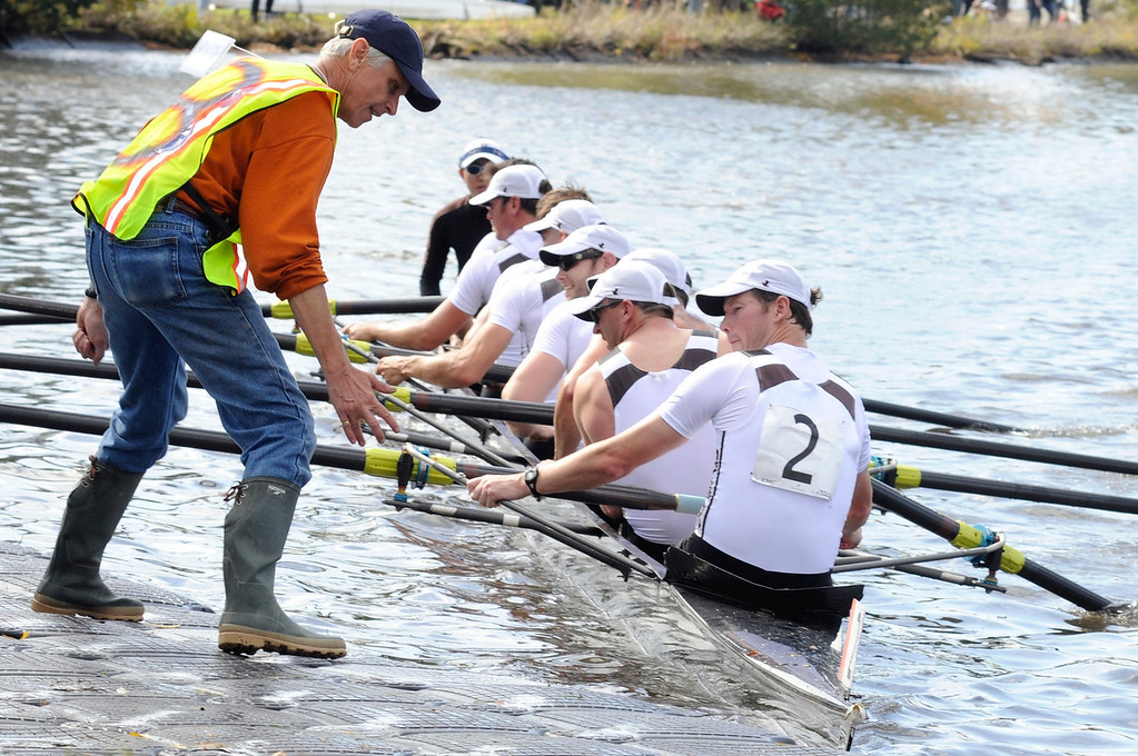 Oct. 20, 2012 - Peter Dirks, a volunteer for the Head of the Charles Regatta, helps a crew team dock their boat after finishing a race on Saturday in Boston, Mass. Dirks said he rowed in high school and became a coach and umpire after graduating from college. Photo by Rachel Schowalter.