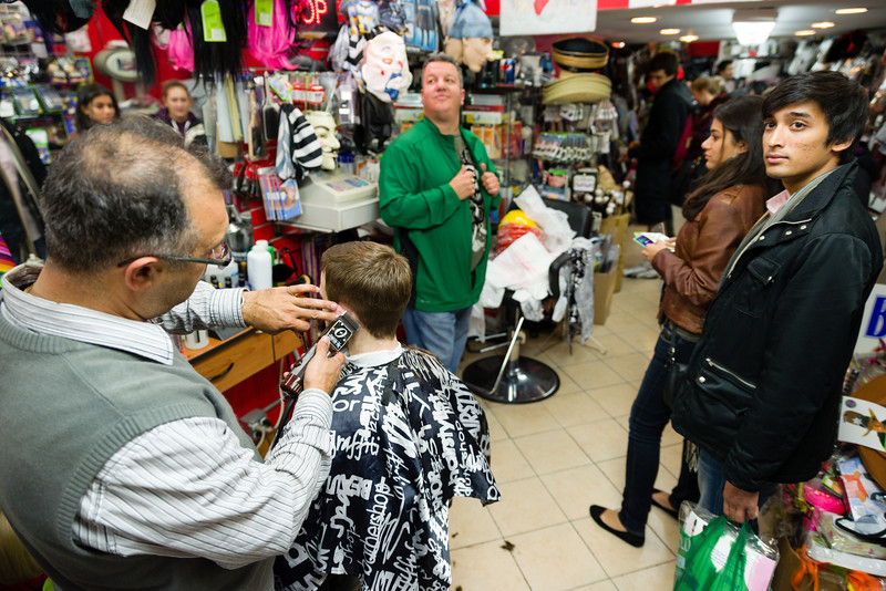 October 25, 2012 - Eduard Achildiyer, 38, cuts a patron's hair at Fast Eddie's Barber Shop as shoppers Lahiru Tholka-Mudalige, right, and Marina Mehrtens wait to pay shop owner Richard Lamoretti, center, for costume items on Thursday night. Both Boston University students at the School of Management, Tholka-Mudalige plans on being a dead surgeon for Halloween and Mehrtens a dead doll. The store, in Lamoretti's family since 1935, attracted a steady stream of customers searching out last-minute costumes before the Halloween weekend. Photo/Christopher Weigl