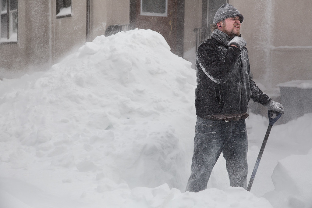 February 9, 2013 - Josh Jenkins of Brighton, MA winces against the wind while shoveling the entry-way to his home on Saturday morning. Winter storm Nemo had dropped over 20 inches of snow on the Boston metro area in the hours before. Photo by Alexa Gonzalez Wagner.