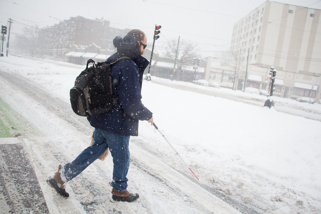 Allston, Feb. 5, 2014 -- John Crary, center left, makes his way across a snowy intersection in Allston, MA. Photograph by Carolyn Bick. © Carolyn Bick/BU News Service 2014.
