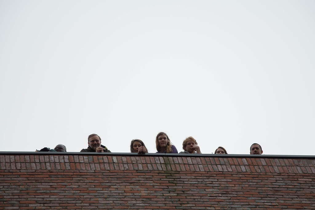 "Boston, Oct. 31, 2013 -- Members of the Boston University Physics Department and others look down from the roof of Boston University's Metcalf Science Center in Boston, MA, before the Boston University Physics Department's 9th annual Pumpkin Drop. The Boston University Physics Department holds the annual Pumpkin Drop on or around Halloween, in which members of the Physics Department push pumpkins filled with paint and whipped cream off the top of the Metcalf Science Center to show that ""gravity still rules"". Photograph by Carolyn Bick."