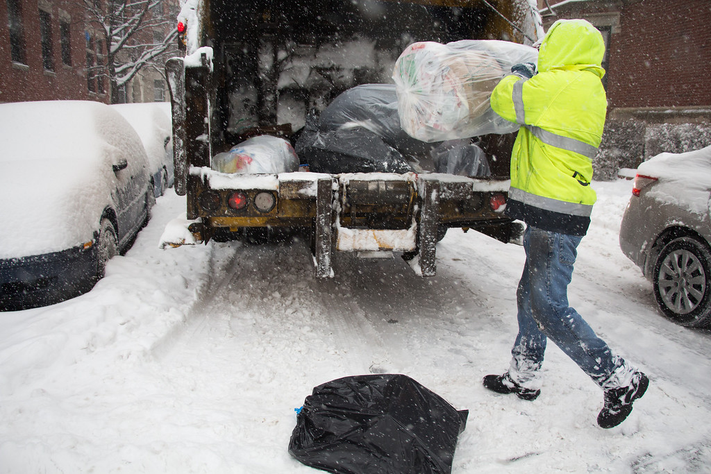 Allston, Feb. 5, 2014 -- Trash collector Mark, right, throws a trash bag into the back of a trash collection truck in Allston, MA, during a snow storm. Mark said he was surprised the city did not suspend trash collection, due to the weather. Photograph by Carolyn Bick. © Carolyn Bick/BU News Service 2014.
