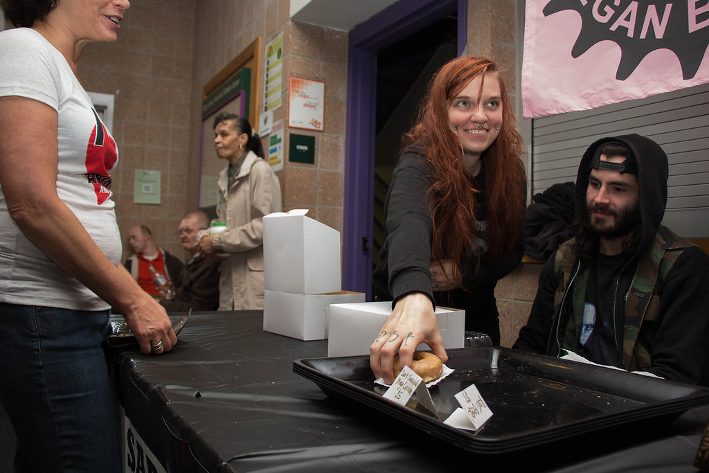 "Boston, Oct. 27, 2013 -- Sabertooth Vegan Bakery owner Evie Noël, center, smiles as she boxes her bakery's last vegan doughnut for Boston Vegetarian Food Festival attendee Sherry Weiland, far left. Noël's friend, Michael Assatly, sits right. ""[I brought] 200 or 300 baked goods yesterday, and sold out in about four hours,"" said Noël. ""Same amount [of pastries] today."" Sabertooth Vegan Bakery also sold out in about four hours on Sunday. Sabertooth Vegan Bakery, based in Jamaica Plain, MA, exhibited at this year's Boston Vegetarian Food Festival in the Reggie Lewis Athletic Center in Boston, MA. Photograph by Carolyn Bick."