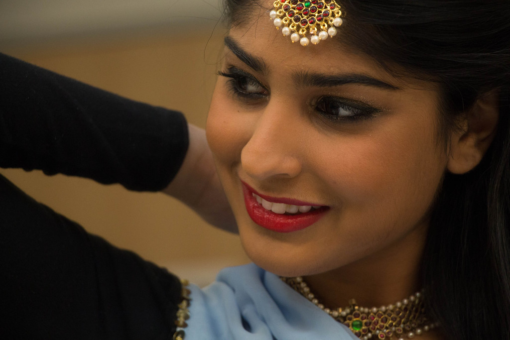 "Boston, Nov. 10, 2013 -- Boston University senior and BU Dheem dancer Aisha Rawji, center, smiles as she fastens her jewelry before BU Dheem's Indian dance presentation entitled, 'Mahila', in Boston University's FitRec dance theatre in Boston, MA. ""This is actually my headwear,"" said Rawji, referring to the piece she fastened around her neck. ""My real necklace is broken."" Rawji said the Indian word 'mahila' means 'women', and that the team chose the title to honor the women in the participating dancers' lives. Dancers from BU, Harvard, and MIT participated in the show. Photograph by Carolyn Bick."