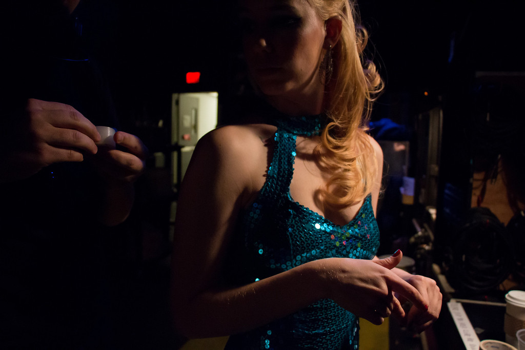 Cambridge, Feb. 7, 2014 -- A stage hand attaches a mic box to  Rogue Burlesque performer Lilly Bordeaux, center, backstage in the Oberon Theatre in Cambridge, MA, before 'Speakeasy Circus'. The night's performance was Bordeaux's last in Massachusetts, before she moves to Atlanta, GA. All members of Rogue Burlesque requested that their stage names be used. Photograph by Carolyn Bick. © Carolyn Bick/BU News Service 2014.