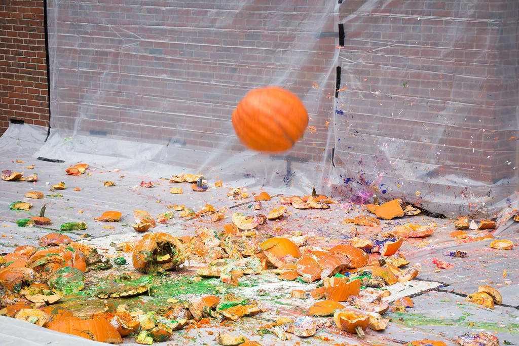"Boston, Oct. 31, 2013 -- The Boston University Physics Department Pumpkin Drop's largest pumpkin drops to the ground during the department's 9th annual Pumpkin Drop. The Boston University Physics Department said this pumpkin weighed 83 lbs. The Boston University Physics Department holds the Pumpkin Drop on or around Halloween, in which members of the Physics Department push pumpkins filled with paint and whipped cream off the top of the Metcalf Science Center to show that ""gravity still rules"". Photograph by Carolyn Bick."