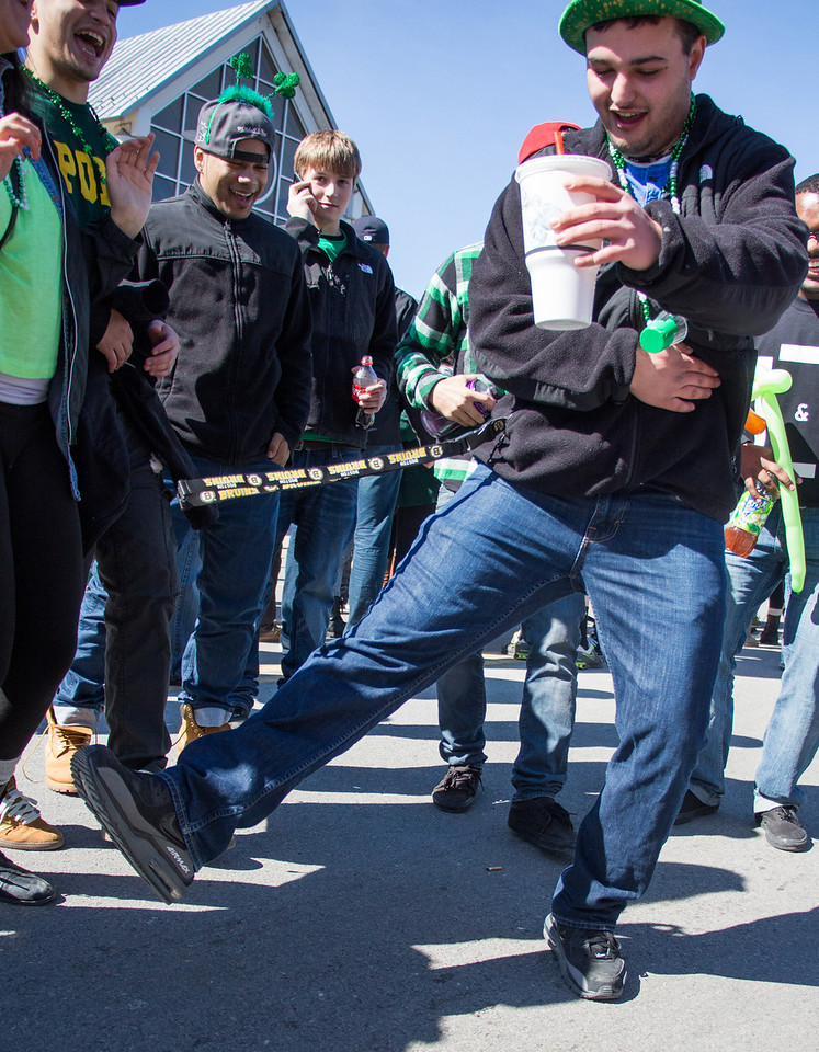 Boston, March 16, 2014 -- Andrew Carter, center right, does a jig near Andrew Station at the St. Patrick's Day parade in South Boston. Photograph by Carolyn Bick. © Carolyn Bick/BU News Service 2014.