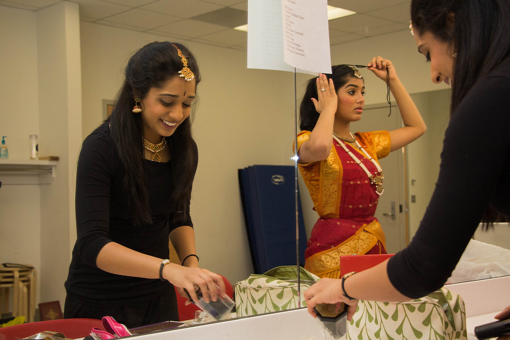 Boston, Nov. 10, 2013 -- Boston University Dheem dancer and BU sohphomore Samantha Venkatesh, left, smiles, while solo dancer and BU junior Ramya Rajpurohit, right,  fixes her head piece before BU Dheem's Indian dance presentation entitled, 'Mahila', in Boston University's FitRec dance theatre in Boston, MA. Dheem dancer and BU senior, Aisha Rawji, not pictured here, said the word 'mahila' means 'women', and that the team chose the title to honor the women in the participating dancers' lives. Dancers from BU, Harvard, and MIT participated in the show. Photograph by Carolyn Bick.