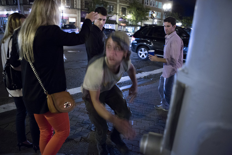 "Sep. 20, 2013 - A 20-year-old homeless man who asked to be identified as Anchor leaps upward in a crowd of pedestrians, scaring them, after crawling on the ground to get in position outside Blanchard's liquor store in Allston. ""People give us dirty looks but at least I don't have to go to a job,"" Anchor said."
