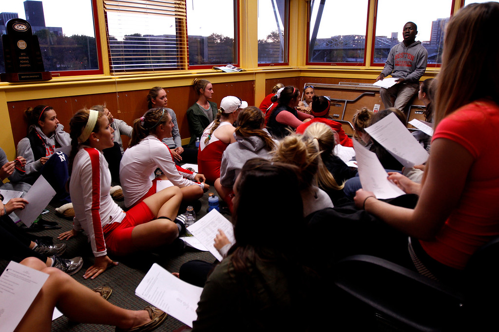 "Boston University Women's Lightweight Coach, Malcolm Doldron explains the ""Phase III"" workout sheet he handed out to the lightweight team after the team completed their first appearance in the Head of the Charles Regatta, the world's largest two-day rowing event in Dewolfe Boathouse in Boston Mass. on Oct. 20, 2013. The 8-person boat and 4-person boat that competed in the race came in 6th and 5th place, with only highly competitive and established crew teams beating them. ""I am pleased with the turnout of their performance, they worked hard. This is our first appearance and it is a good start."" Photo by Grace Donnelly."