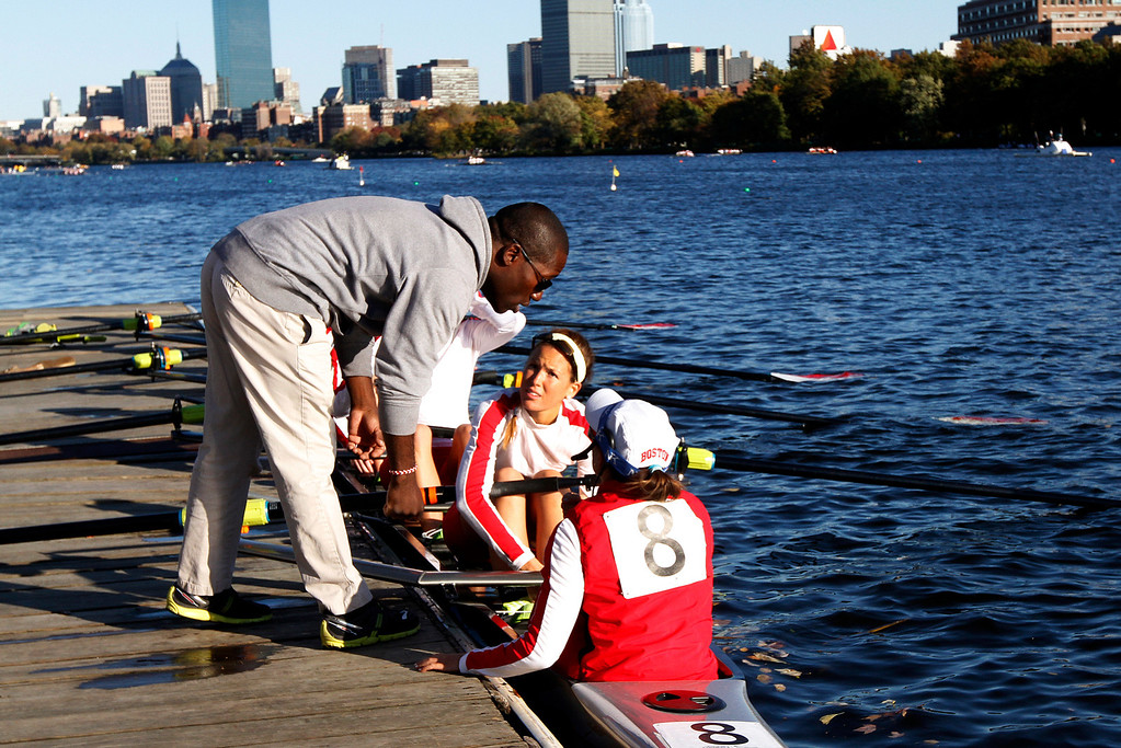 Boston University Women's Lightweight Coach, Malcolm Doldron gives two women's lightweight team members a few last-minute words of encouragement before, the team makes its' programs first appearance at the Head of the Charles Regatta, the world's largest two-day rowing event on Oct. 20, 2013 at Dewolfe Boathouse in Boston, Mass. Photo by Grace Donnelly.