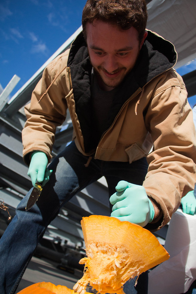 "Boston, Oct. 29, 2013 -- Boston University physics graduate student Dan Arcaro, center, takes the top off a pumpkin on top of the Metcalf Science Center at Boston University in Boston, MA, two days before the Boston University Physics Department's 9th annual Pumpkin Drop. The Boston University Physics Department holds its annual Pumpkin Drop on or around Halloween, in which members of the Physics Department push pumpkins filled with paint and whipped cream off the top of the Metcalf Science Center to show that ""gravity still rules"". Photograph by Carolyn Bick."