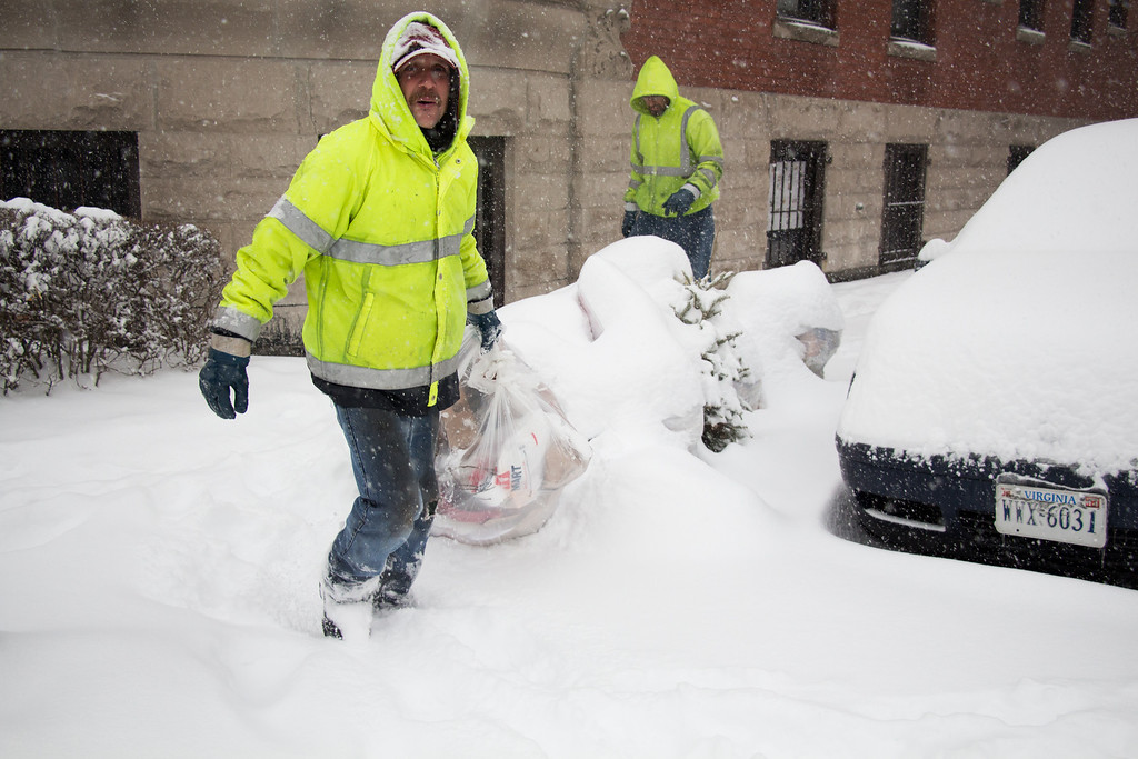 Allston, Feb. 5, 2014 -- Trash collectors Mark, left, and Dave, back right, pick up trash on a street in Allston, MA, during a snow storm. Mark said he was surprised the city did not cancel trash collection, because of the weather. Photograph by Carolyn Bick. © Carolyn Bick/BU News Service 2014.
