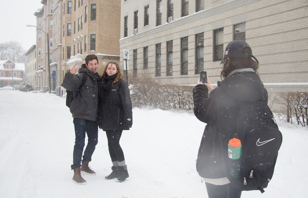 Allston, Feb. 5, 2014 -- Boston University student Erin Pierce, right, takes photos of David Lacle, left, and Rachel Walden, center left. 'This is [Lacle's] first snowstorm,' said Walden. 'He's from Aruba.' Photograph by Carolyn Bick. © Carolyn Bick/BU News Service 2014.