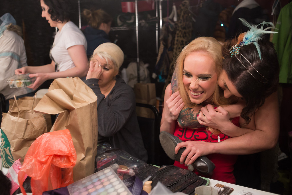 Cambridge, Feb. 7, 2014 -- Laa Ceradona, back right, hugs Rogue Burlesque performer Lilly Bordeaux, front right, in the Oberon Theatre's dressing room in Cambridge, MA. The night's performance was Bordeaux's last in Massachusetts, before she moves to Atlanta, GA. All members of Rogue Burlesque requested that their stage names be used. Photograph by Carolyn Bick. © Carolyn Bick/BU News Service 2014.