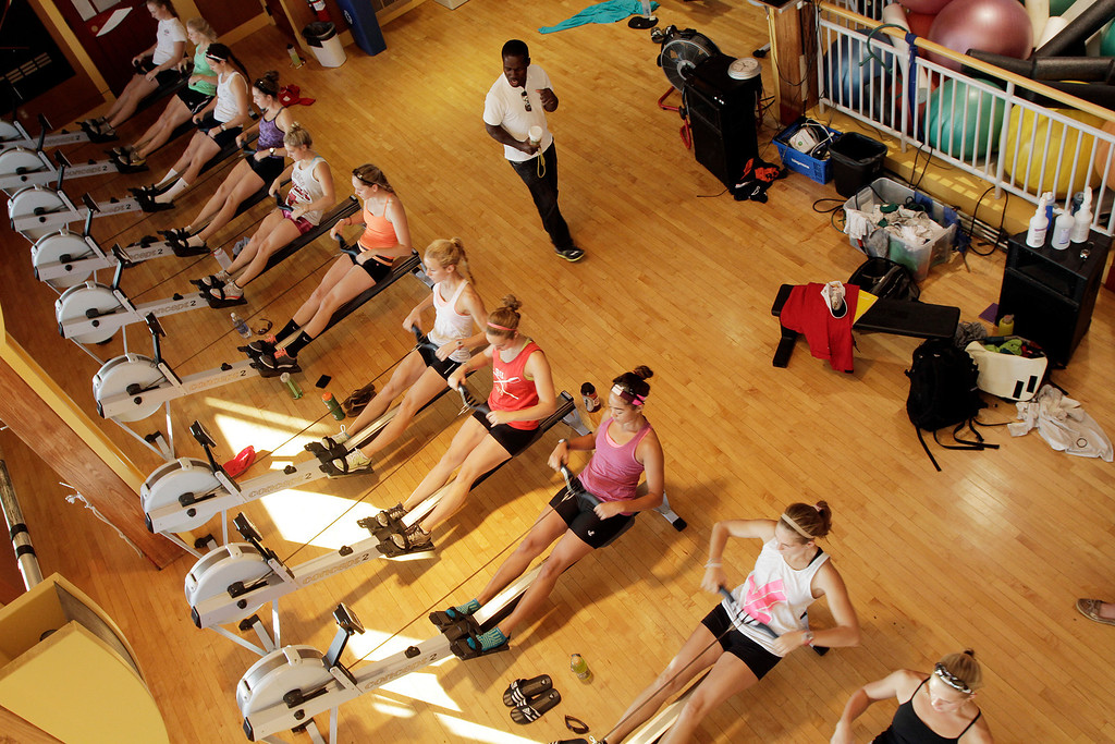 Boston University Women's Lightweight Coach, Malcolm Doldron monitors his Lightweight team during their warm-up on the erg machines at BU's Dewolfe Boathouse on Oct. 17, 2013. This is the last, coached practice before the new lightweight program's first appearance in the Head of the Charles Regatta, the world's largest two-day rowing event. Photo by Grace Donnelly.