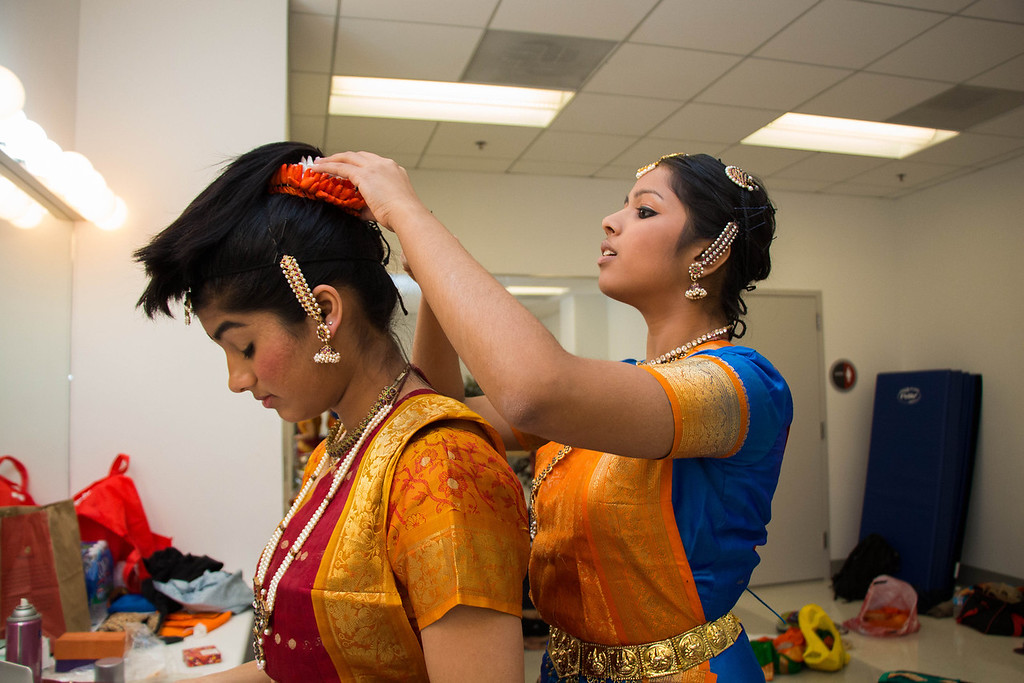 Boston, Nov. 10, 2013 -- Boston University solo dancer and BU senior Janani Ramachandran, center right, helps solo dancer and BU junior Ramya Rajpurohit, center left, fix her head piece before BU Dheem's Indian dance presentation entitled, 'Mahila', in Boston University's FitRec dance theatre in Boston, MA. Dheem dancer and BU senior, Aisha Rawji, not pictured here, said the word 'mahila' means 'women', and that the team chose the title to honor the women in the participating dancers' lives. Dancers from BU, Harvard, and MIT participated in the show. Photograph by Carolyn Bick.