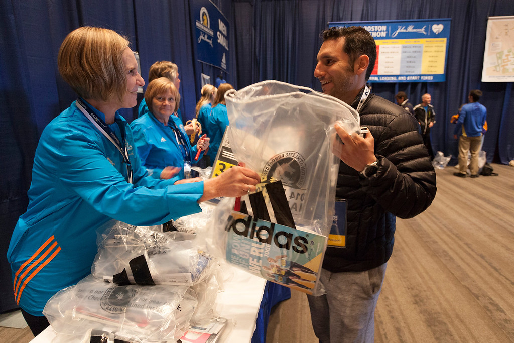 April 19, 2014. Roberto Gonzalez, from Mexico, picks up his Boston Marathon t-shirt at the Hynes Convention Center in Boston, Mass. Photo by Dominique Riofrio.