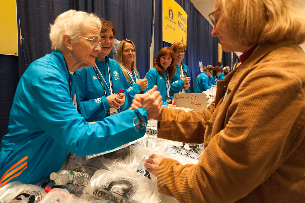 April 19, 2014. Volunteers give support to runners as they pick up their Marathon t-shirts at the Hynes Convention Center in Boston, Mass. Photo by Dominique Riofrio.