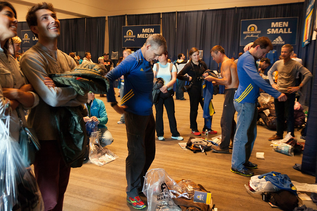 April 19, 2014. Jeremy Griffiths (center), from Toronto, tries on his Boston Marathon t-shirt at the Hynes Convention Center in Boston, Mass. Photo by Dominique Riofrio.