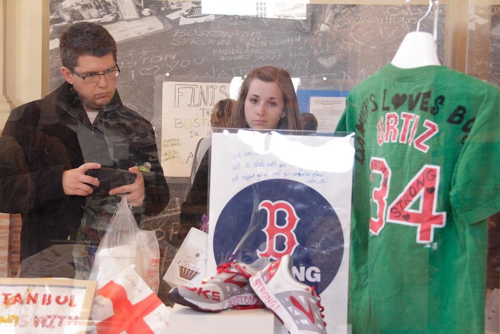 April 16, 2014--Boston, Mass. Matt Caron, right, and Amanda Ness, center, look at display of a Boston Marathon memorial from Istanbul in the Dear Boston Exhibit at Boston Public Library. Photo by Andrea Betenia.