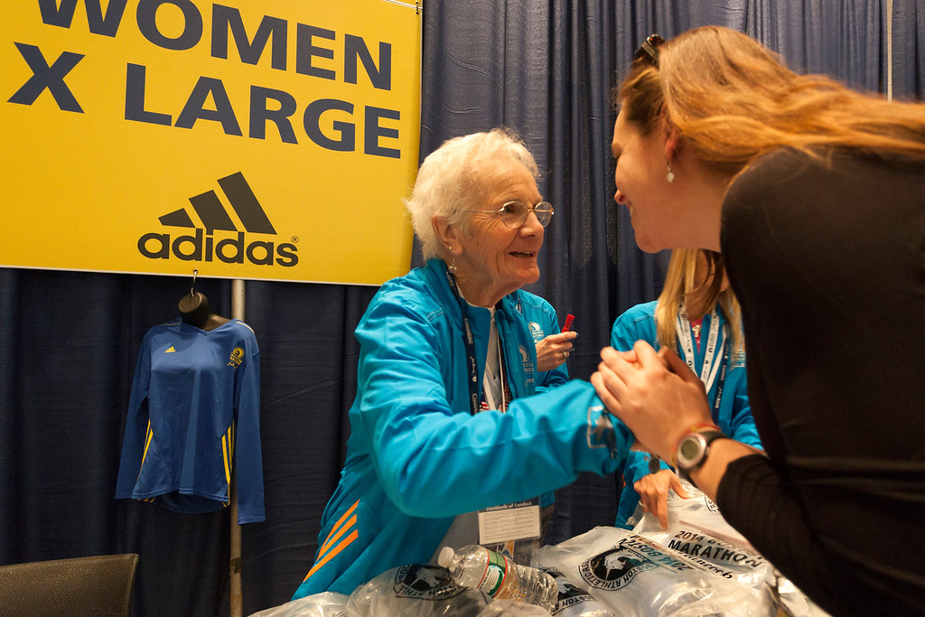 April 19, 2014. Volunteer Harriet Patoh gives support to runners as they pick up their Marathon t-shirts at the Hynes Convention Center in Boston, Mass. Photo by Dominique Riofrio.