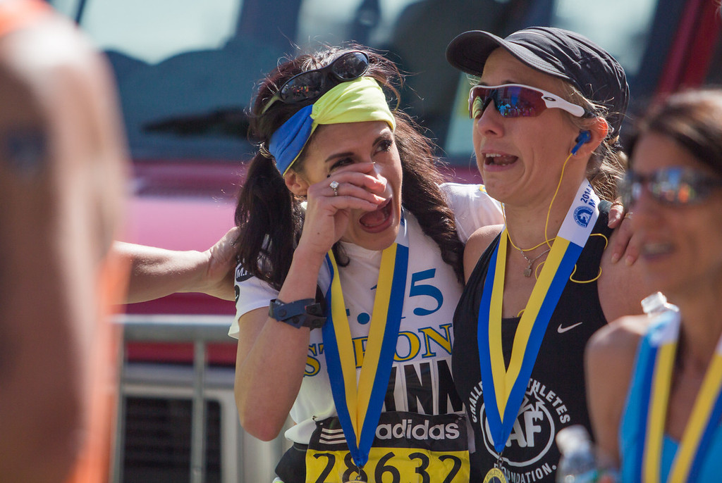 "April 21, 2014 -- Boston Marathon bombing survivor Lynn Crisci, center, wipes away tears as she is physically supported by Sarah Reinertsen, an American triathlete and former Paralympic track athlete. Crisci said Reinertsen helped her finish the race by walking the last several miles with her. ""I couldn't have done it without her,"" said Crisci. Crisci, who participated in the Boston, Mass., Marathon for the first time this year, lives a connective tissue disorder, two brain injuries, and chronic pain. Photograph by Carolyn Bick/BU News Service."