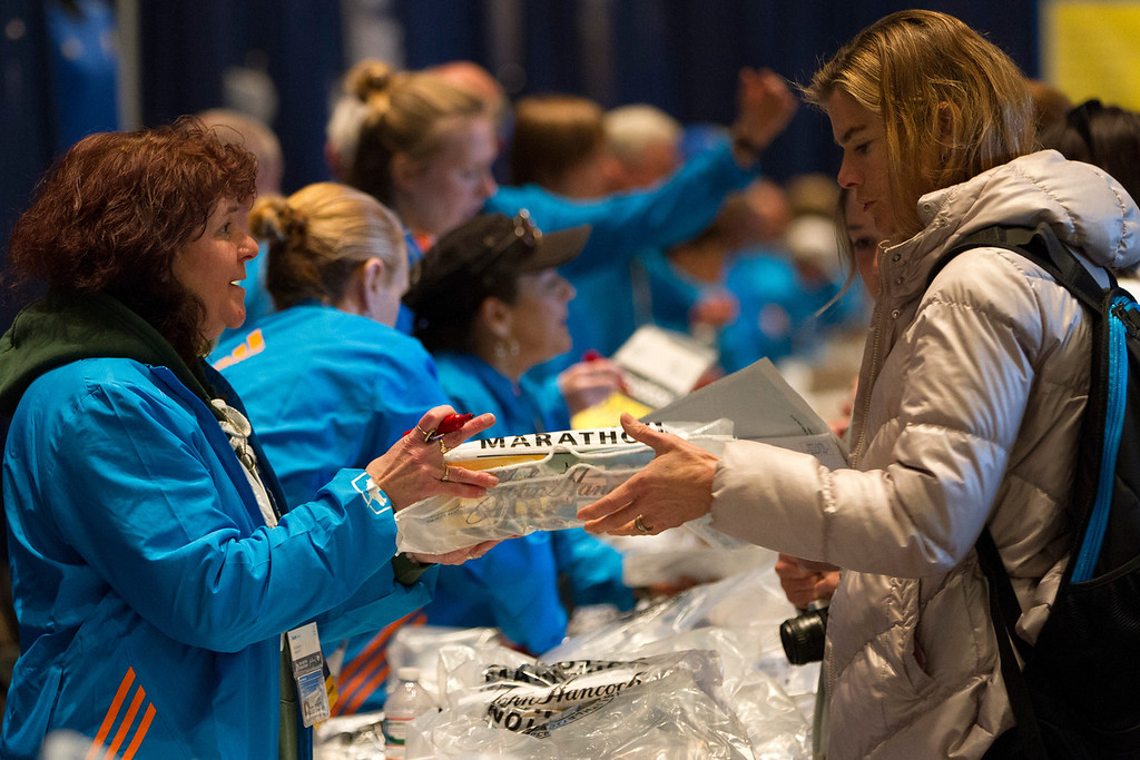April 19, 2014. Runners pick up their Boston marathon t-shirt at the Marathon Expo which took place at the Hynes Convention Center in Boston, Mass. Photo by Dominique Riofrio.