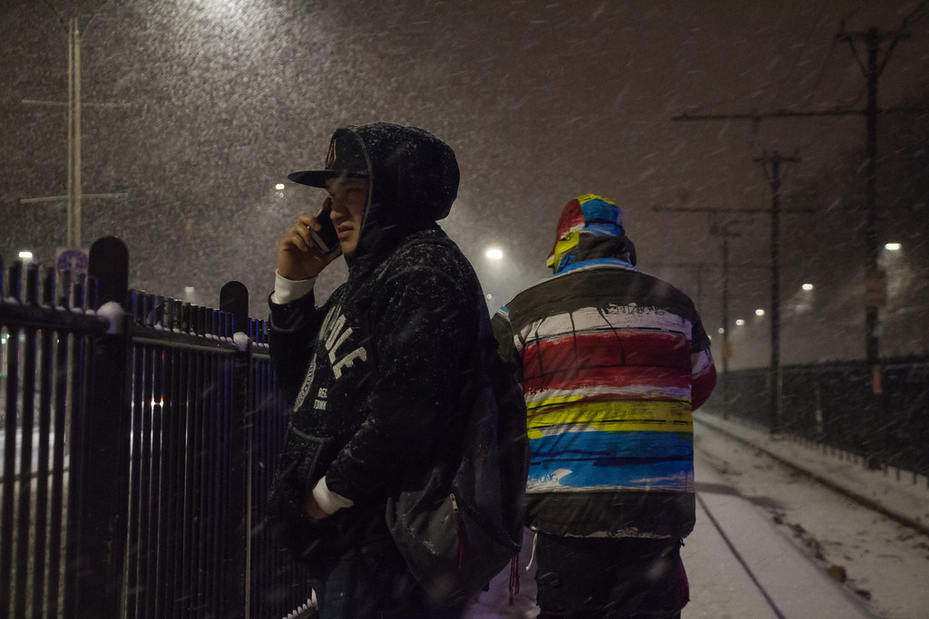 Allston, Jan. 21, 2014 -- Marco Lopez, center left, talks on his cell phone while waiting for a B Line train at the Harvard Avenue station in Allston, MA. The El Salvadorian native said that, while he likes the winter weather, he did not wear the right jacket for Winter Storm Janus. 'My jacket's already soaked,' said Lopez. Photograph by Carolyn Bick. ©BU News Service/Carolyn Bick 2014.