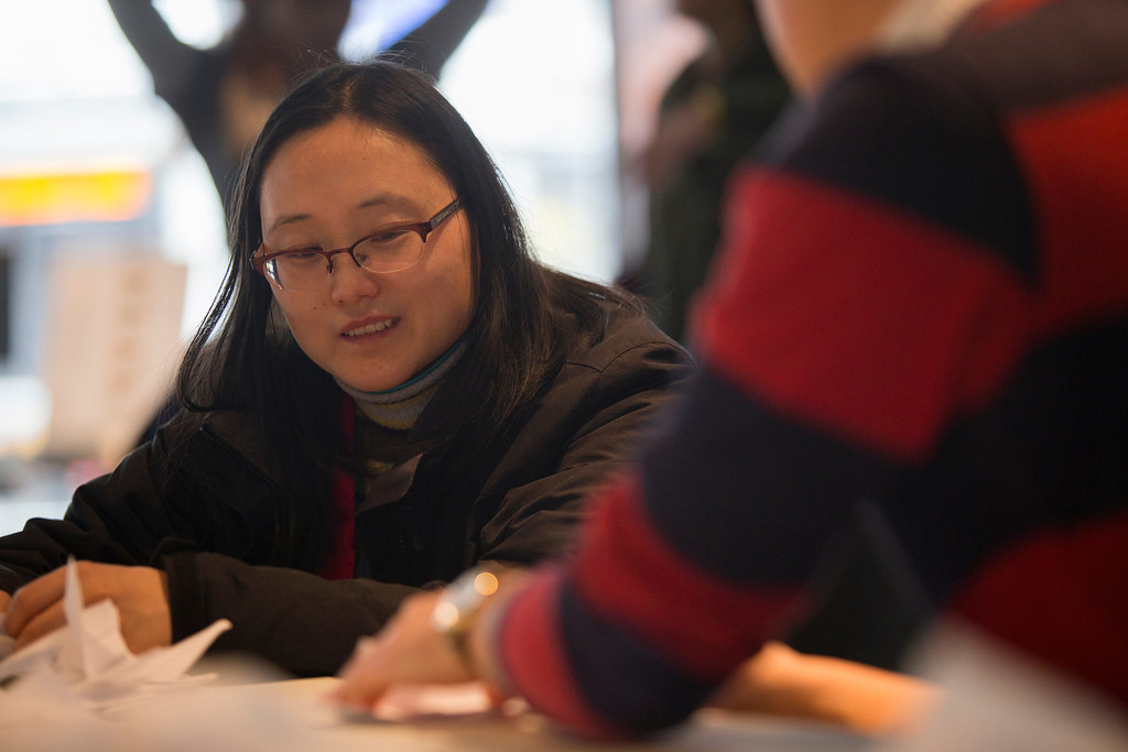 April 5, 2014 – Chunyan Yuan, left, watches the MIT Museum's public programs coordinator Andrew Hong, right, fold a paper crane during a crane-folding event for Cranes for Collier, an installation project dedicated to MIT Police Officer Sean Collier who was killed by the two suspects responsible for the Boston Marathon bombings last year, at the MIT Museum at 265 Massachusetts Ave., in Cambridge, Mass. Photo by Jun Tsuboike/BU News Service