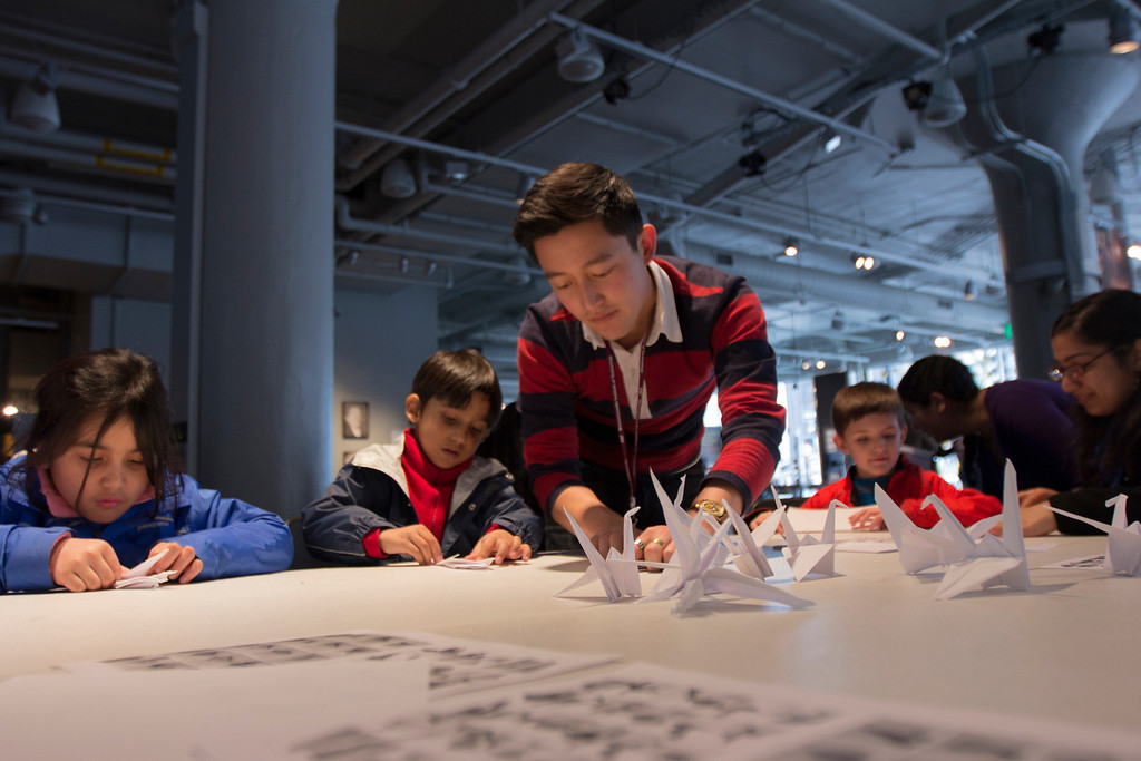 April 5, 2014 – The MIT museum's public programs coordinator Andrew Hong, center, teaches museum visitors how to fold paper cranes during a crane-folding event for Cranes for Collier, an installation project dedicated to MIT Police Officer Sean Collier who was killed by the two suspects responsible for the Boston Marathon bombings last year, at the MIT Museum at 265 Massachusetts Ave., in Cambridge, Mass. Photo by Jun Tsuboike/BU News Service