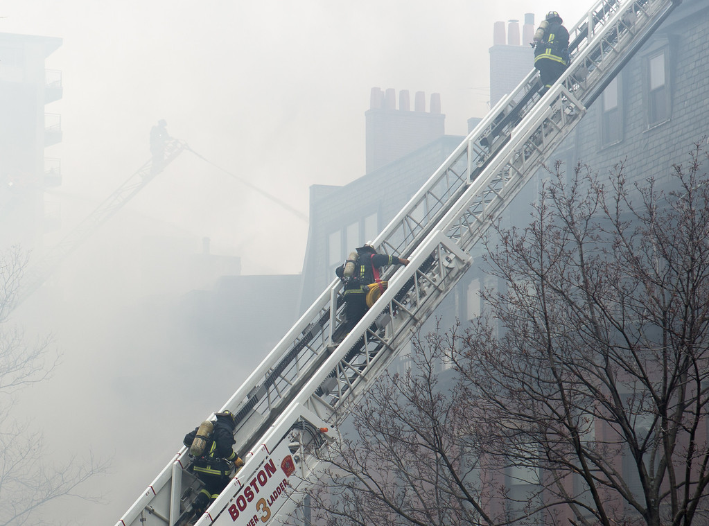 March 26, 2014 - Firefighters climb a ladder while responding to a 9-alarm fire on Beacon Street in Boston, Mass.