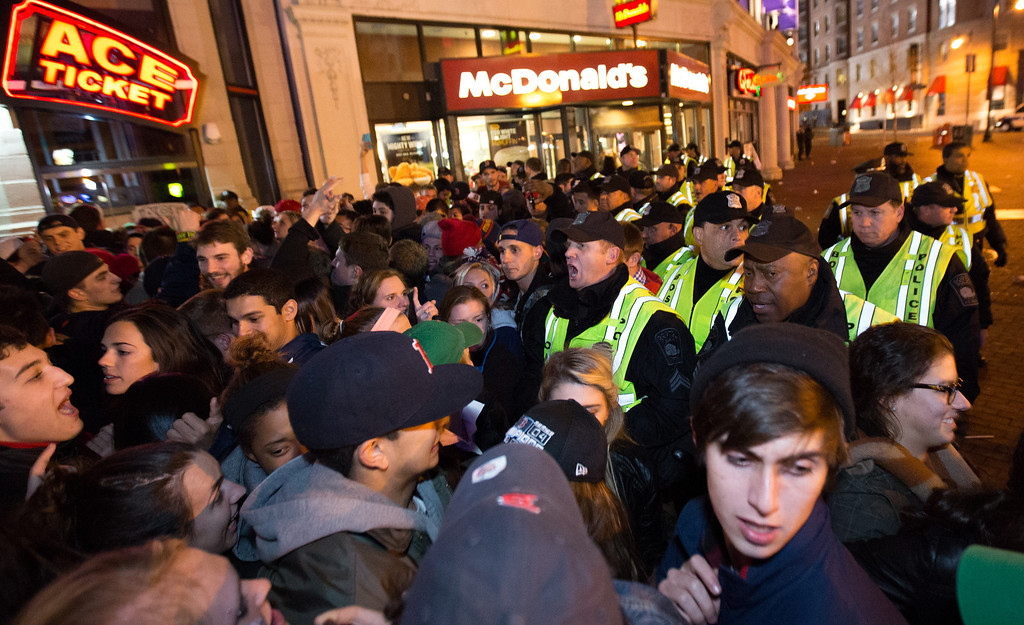 Oct. 30, 2013 - Boston Police officers push back crowds that gathered for a celebration that followed  a Red Sox World Series win at Fenway Park in Boston. Photo by Justin Saglio.