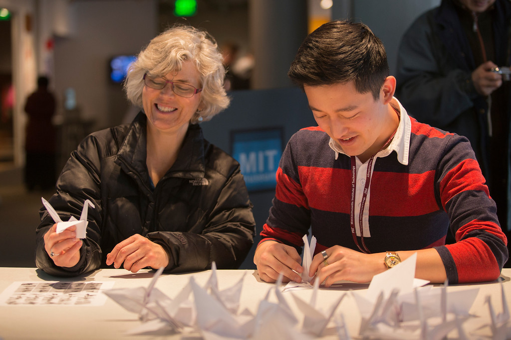April 5, 2014 – Kathy Proctor, left, reacts to her paper crane after being instructed by the MIT Museum's public programs coordinator Andrew Hong, right, during a crane-folding event for Cranes for Collier, an installation project dedicated to MIT Police Officer Sean Collier who was killed by the two suspects responsible for the Boston Marathon bombings last year, at the MIT Museum at 265 Massachusetts Ave., in Cambridge, Mass. Photo by Jun Tsuboike/BU News Service