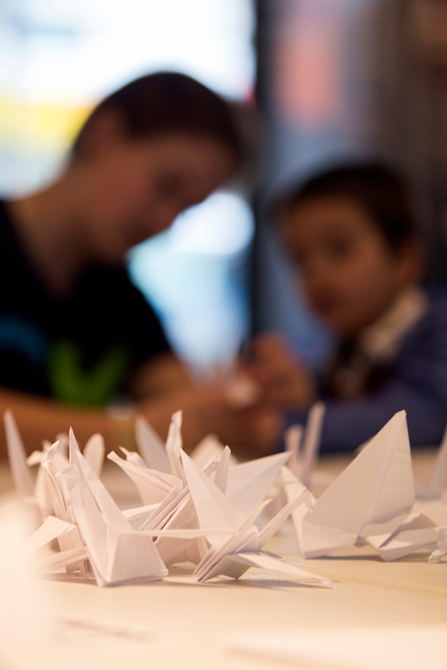 April 5, 2014 – Paper cranes are laid in the center of the table during a crane-folding event for Cranes for Collier, an installation project dedicated to MIT Police Officer Sean Collier who was killed by the two suspects responsible for the Boston Marathon bombings last year, at the MIT Museum at 265 Massachusetts Ave., in Cambridge, Mass. Photo by Jun Tsuboike/BU News Service