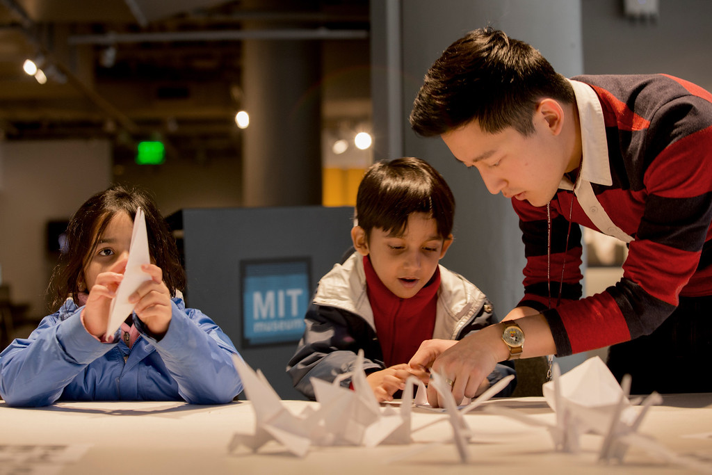 April 5, 2014 – The MIT Museum's public programs coordinator Andrew Hong, right, teaches 6-year-olds Suhayl Samir, center, and Saira Alwi, left, how to fold paper cranes during a crane-folding event for Cranes for Collier, an installation project dedicated to MIT Police Officer Sean Collier who was killed by the two suspects responsible for the Boston Marathon bombings last year, at the MIT Museum at 265 Massachusetts Ave., in Cambridge, Mass. Photo by Jun Tsuboike/BU News Service