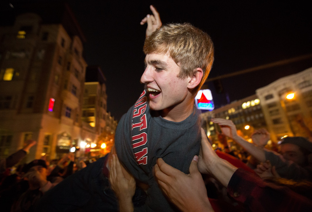 Oct. 30, 2013 - Students in the Kenmore Square area of Boston raise another student in the air in celebration after learning the Red Sox had won the World Series with a victory at Fenway Park in Boston. Photo by Justin Saglio.