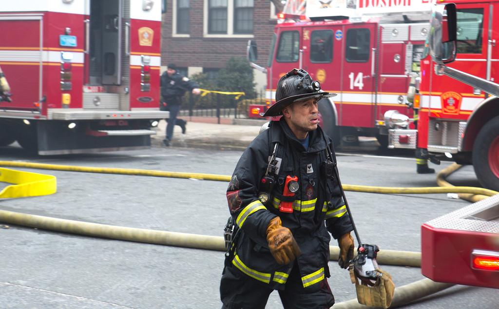 March 26, 2014 - A firefighter responds to a 9-alarm fire on Beacon Street in Boston, Mass.