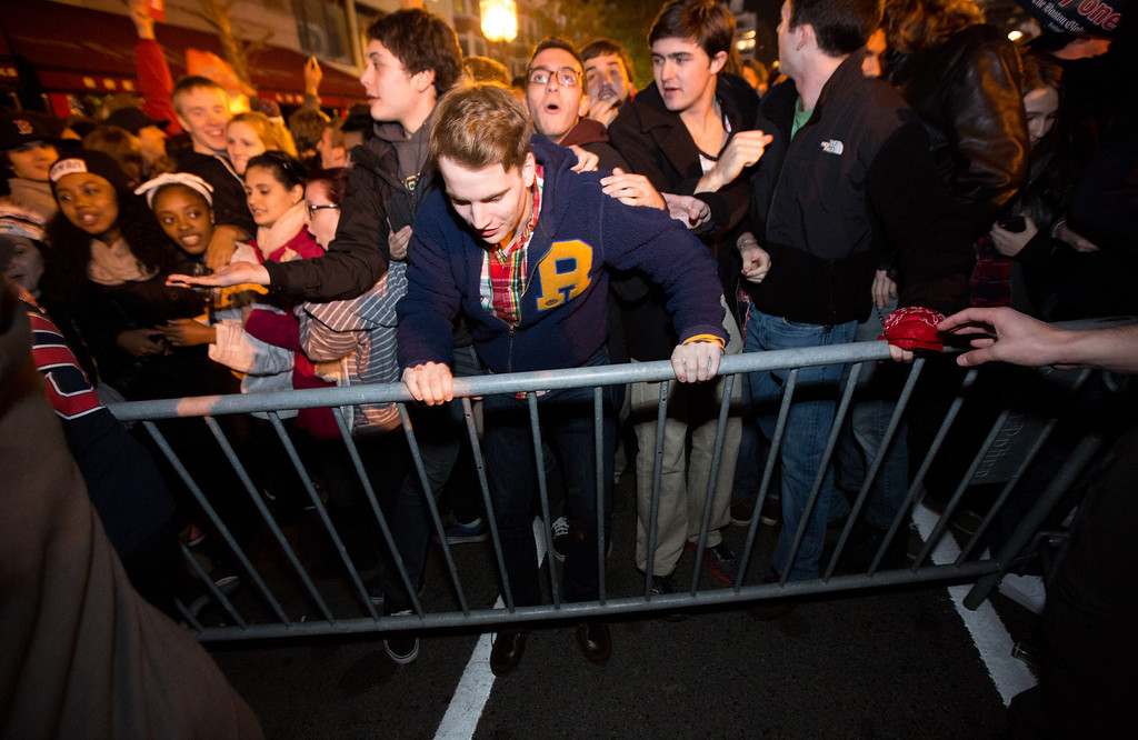 Oct. 30, 2013 - Students in the Kenmore Square area of Boston topple police barriers after learning the Red Sox had won the World Series with a victory at Fenway Park in Boston. Photo by Justin Saglio.