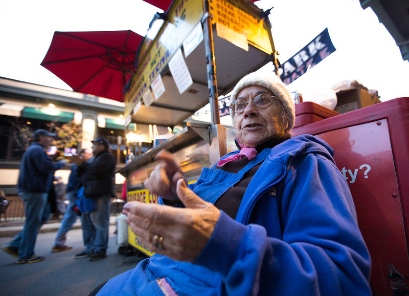 Oct. 23, 2013 - Eleni Patiras, owner of a sausage stand outside Fenway Park, talks with customers before the first game of the World Series in Boston. Photo by Justin Saglio