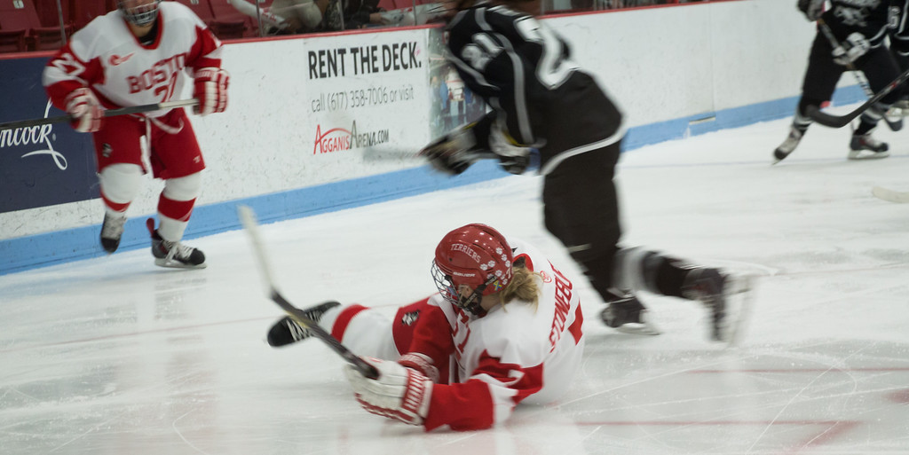 Boston, March 1, 2014 -- Boston University women's hockey defense Shannon Stoneburgh, center, falls during the East Quarterfinals against Providence College. The game was held at Boston University's Walter Brown Arena in Boston, MA. BU won 3-2. Photograph by Carolyn Bick. © Carolyn Bick/BUNS 2014.