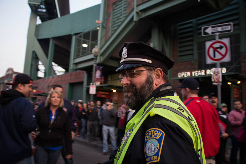 Boston, Oct. 30, 2013 -- Steve Horgan, center right, dubbed 'Bullpen Cop', walks down Lansdowne Street near Fenway Park in Boston, MA. The Boston Red Sox played against the St. Louis Cardinals at Fenway Park in the 6th game of the World Series. Photograph by Carolyn Bick.