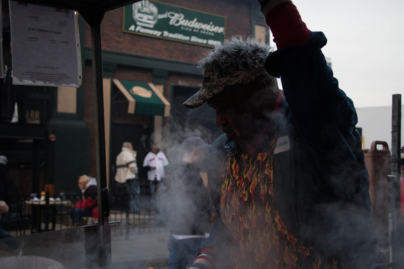 Boston, Oct. 30, 2013 -- George Greenidge, right, cooks sausages for baseball fans outside Fenway Park in Boston, MA. The Boston Red Sox played against the St. Louis Cardinals at Fenway Park in the 6th game of the World Series. Photograph by Carolyn Bick.