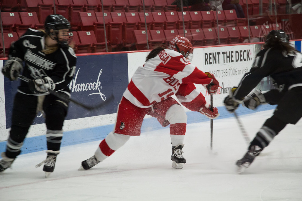 Boston, March 1, 2014 -- Boston University women's hockey defense Lillian Ribeirinha-Braga, center, and Providence College women's hockey defense Victoria Virtue, left, and forward Haley Frade, right, play in the Women's Hockey East Quarterfinals. The game was held at Boston University's Walter Brown Arena in Boston, MA. BU won 3-2. Photograph by Carolyn Bick. © Carolyn Bick/BUNS 2014.
