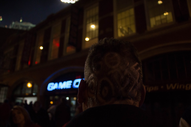 Boston, Oct. 30, 2013 -- Tony Picard talks with friends outside Fenway Park in Boston, MA. Picard said he shaved his head himself. The Boston Red Sox played against the St. Louis Cardinals at Fenway Park in the 6th game of the World Series. Photograph by Carolyn Bick.