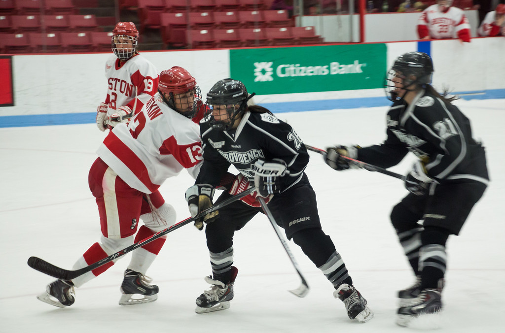 Boston, March 1, 2014 -- Boston University women's defense Kaleigh Fratkin, front left, and Providence College women's hockey forwards Allison Micheletti, center, and Haley Frade, right, play during the East Quarterfinals. The game was held at Boston University's Walter Brown Arena in Boston, MA. BU won 3-2. Photograph by Carolyn Bick. © Carolyn Bick/BUNS 2014.