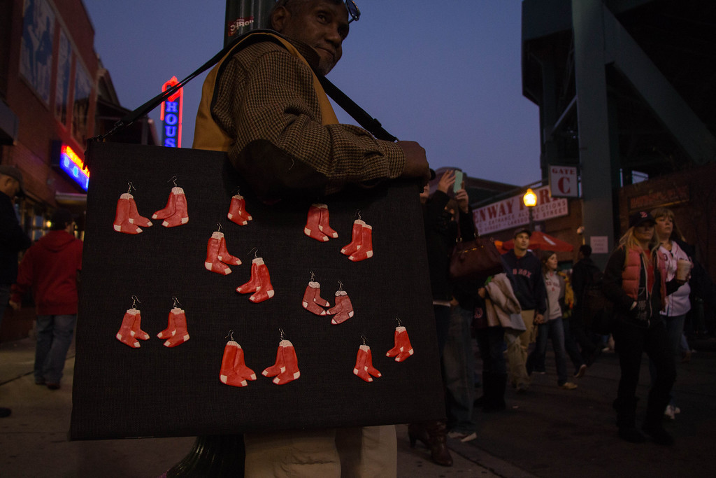 Boston, Oct. 30, 2013 -- Mike Pierce, center left, carries Red Sox ornaments for sale outside Fenway Park in Boston, MA. The Boston Red Sox played against the St. Louis Cardinals at Fenway Park in the 6th game of the World Series. Photograph by Carolyn Bick.